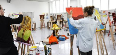 To elever som maler på lerret på staffeli