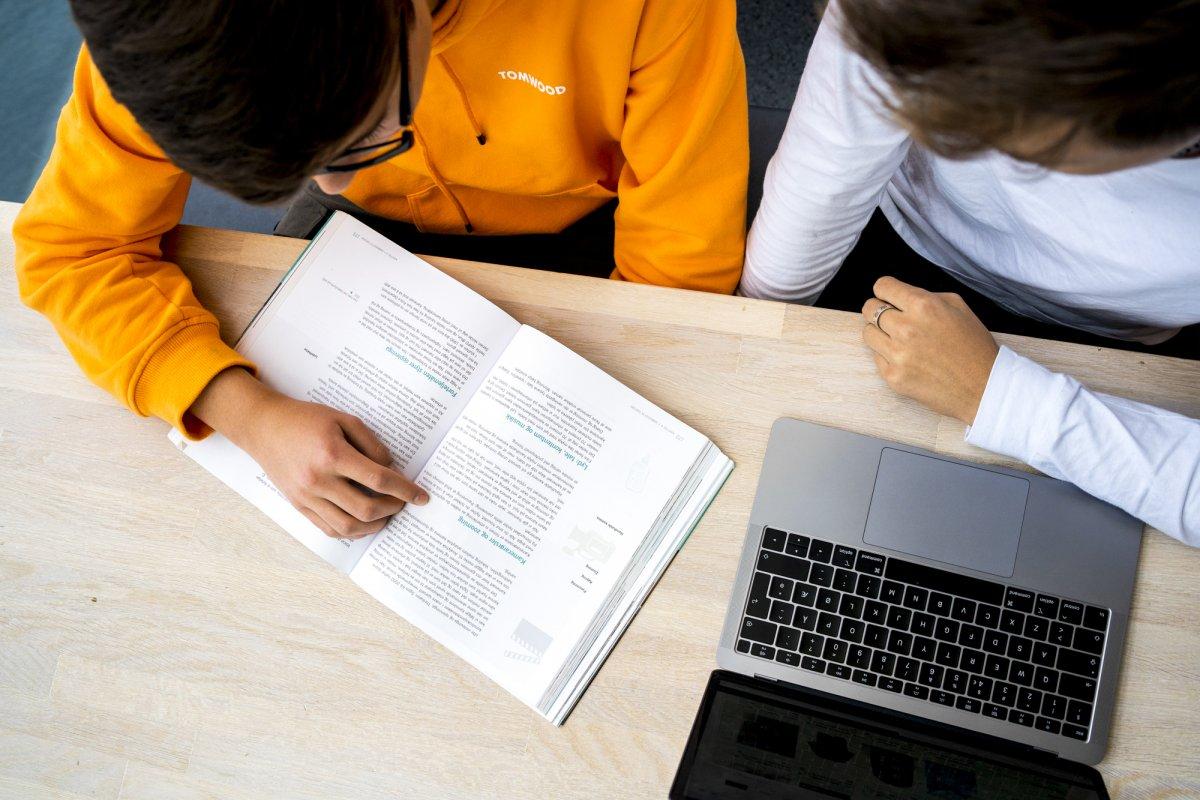To Akademiet-elever som jobber på Mac ved bord. Foto.