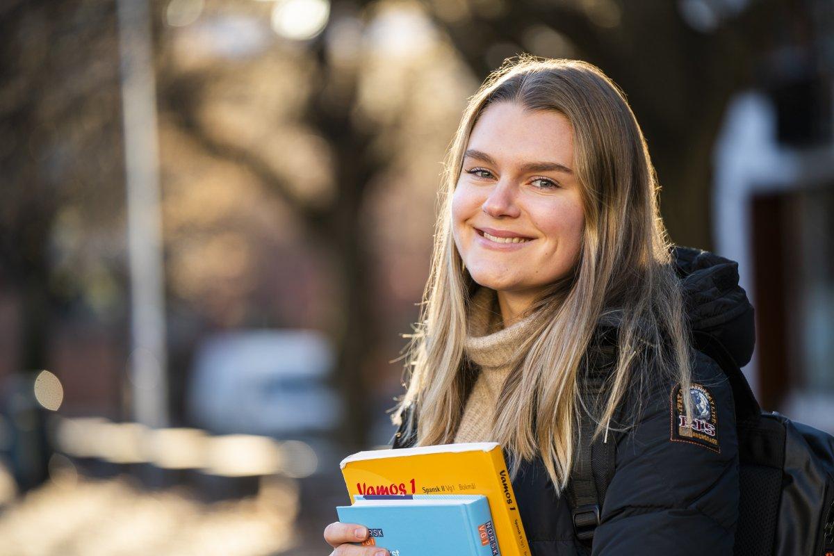 Elev ved Akademiet Nettstudier ute, smiler og holder bøker. Foto.